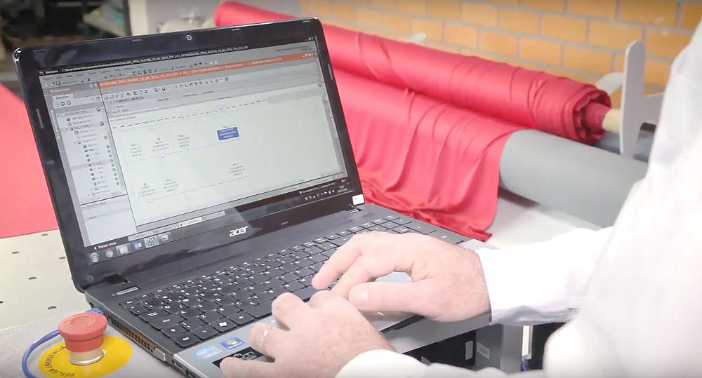 Pessoa operando processos de produção têxtil em um computador.