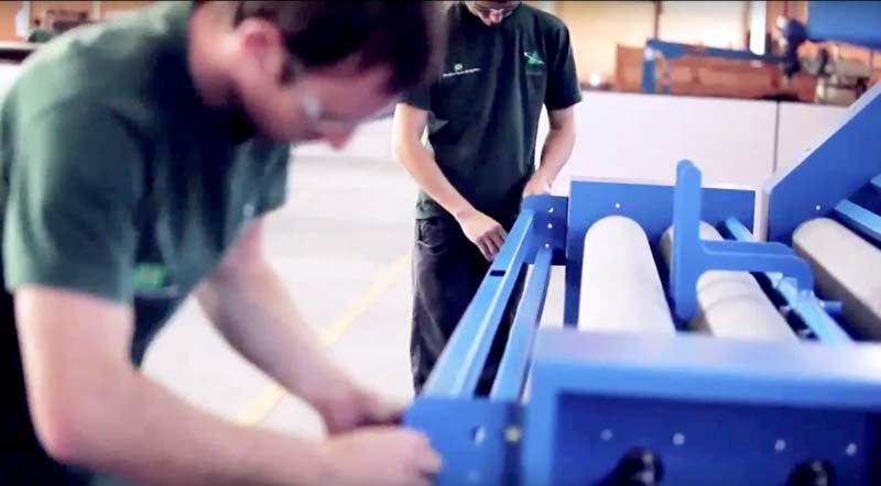 Dois funcionários trabalhando em uma máquina realizando manutenção industrial têxtil.